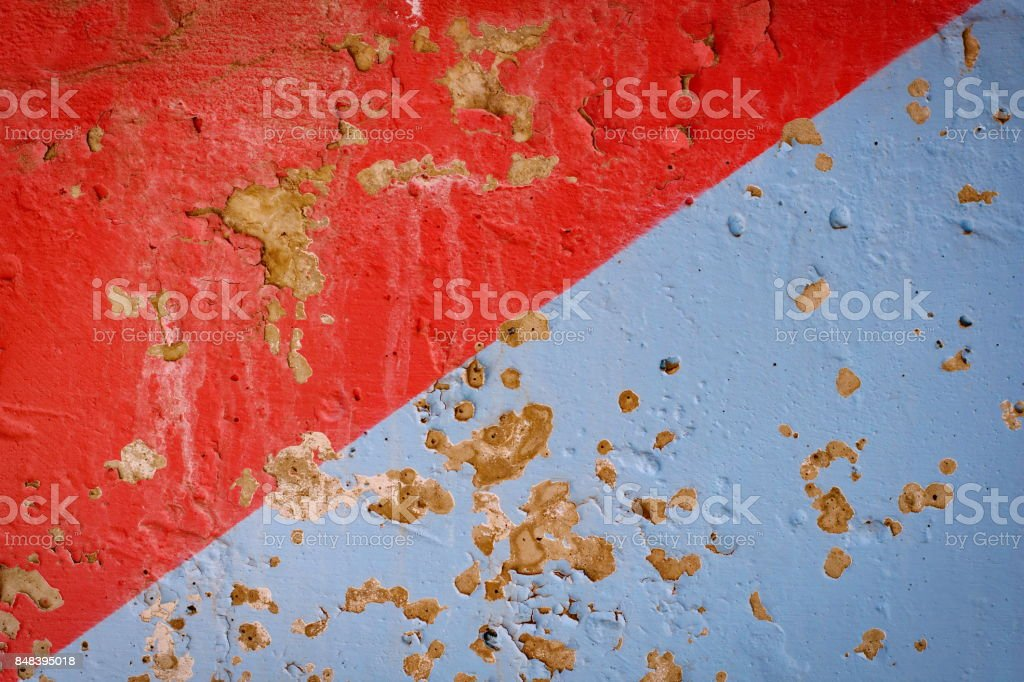 Background of a stucco coated and painted exterior, diagonal red and blue, rough cast of cement and concrete wall texture stock photo