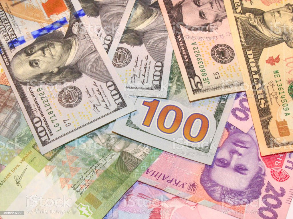 background of American dollars and grivnas bank notes stock photo