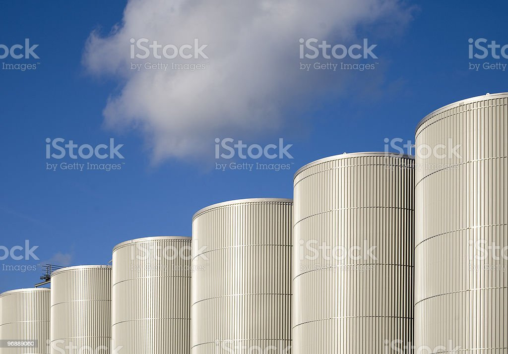 Background of azure skies with rows of storage tanks stock photo