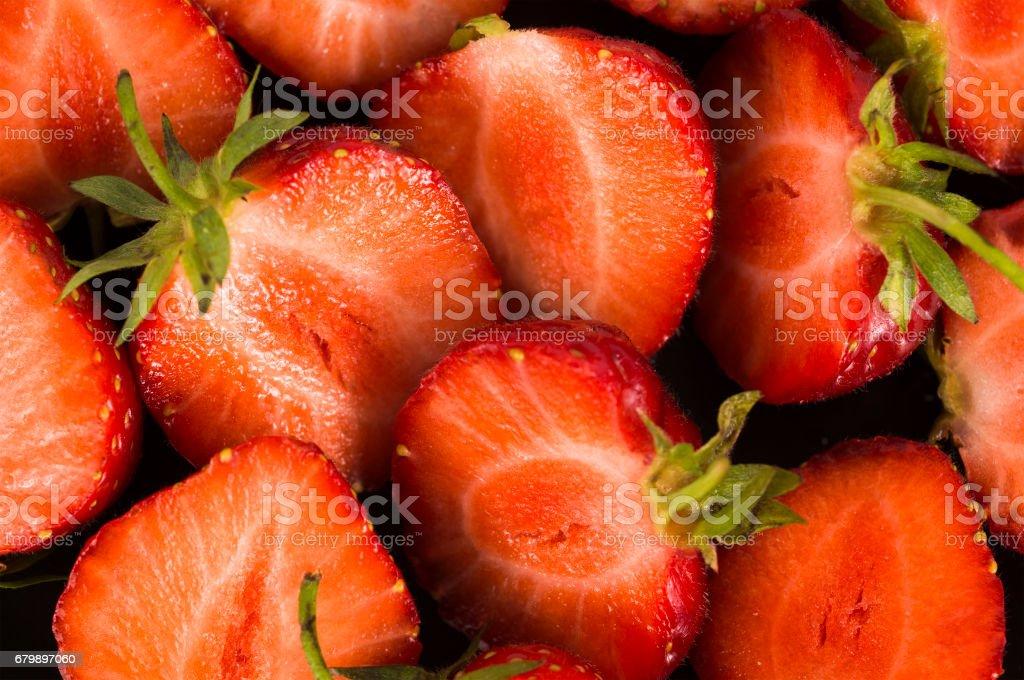 Background of fresh cut strawberries. Ripe strawberries close-up. stock photo