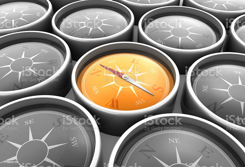 Background of gray compasses with one orange compass royalty-free stock photo