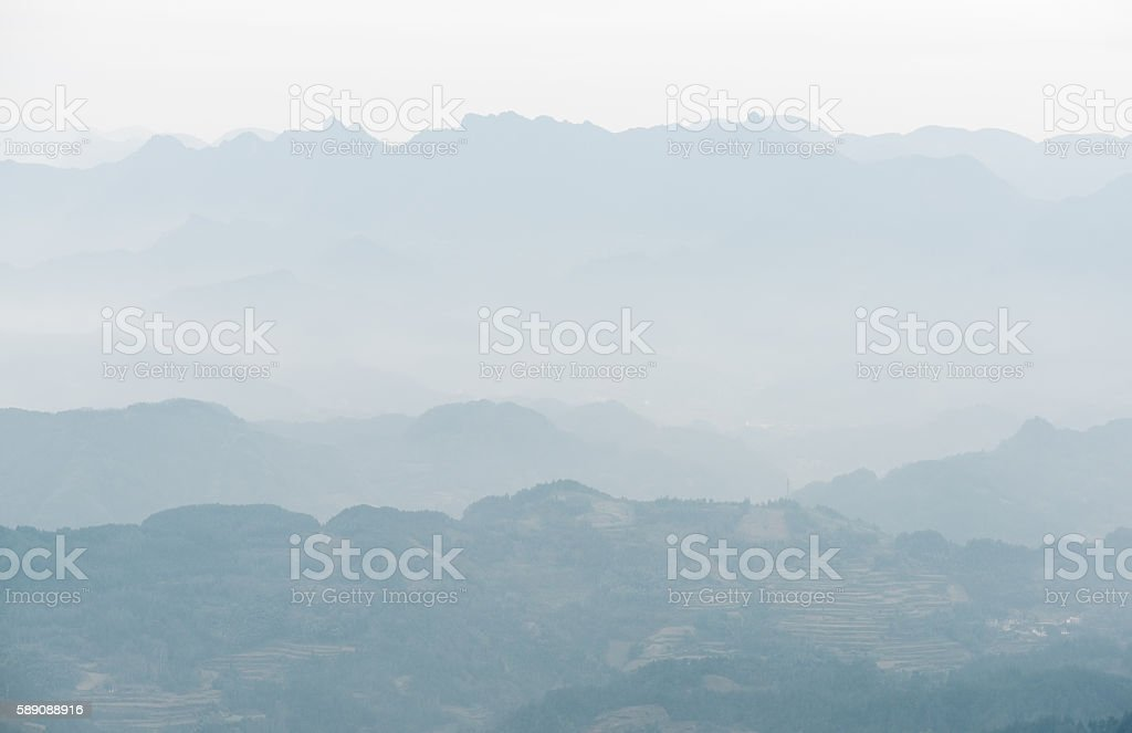 Background of haze-shrouded mountains. View of mountains in mist stock photo