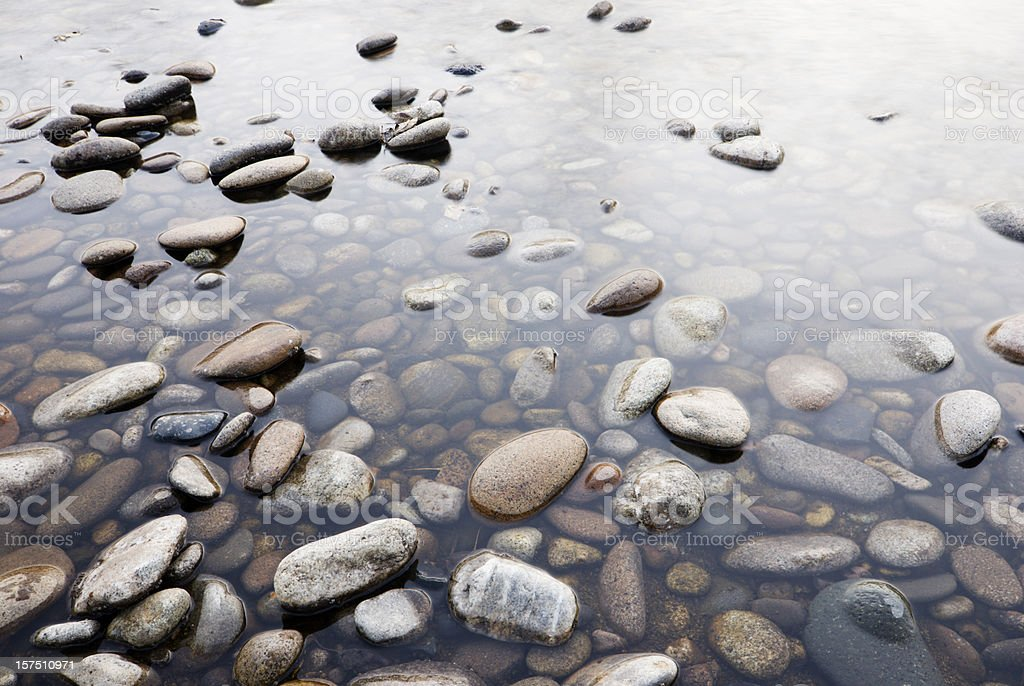 Background of pebbles in shallow water stock photo