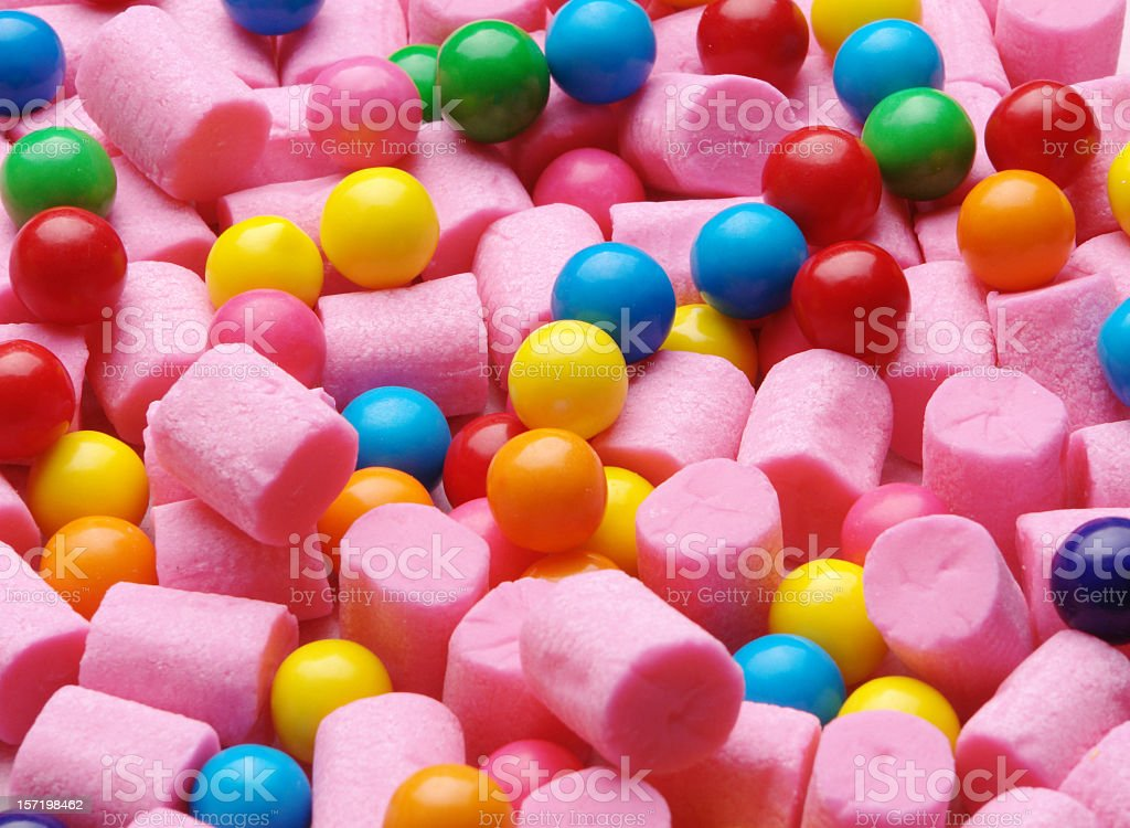 Background of pink cylinder shaped gum and colorful gumballs stock photo