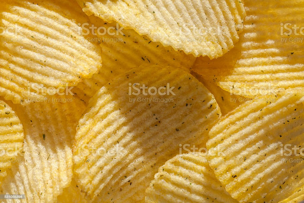 Background of ridged potato chips with spices. Closeup stock photo