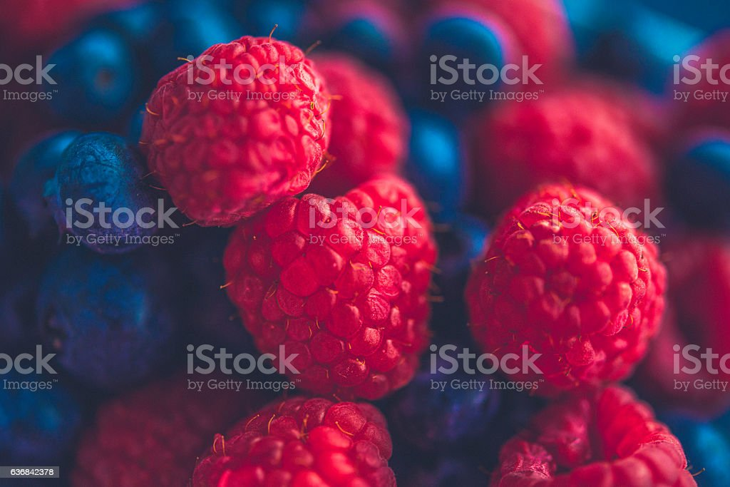 Background of vibrant raspberries and blueberries stock photo