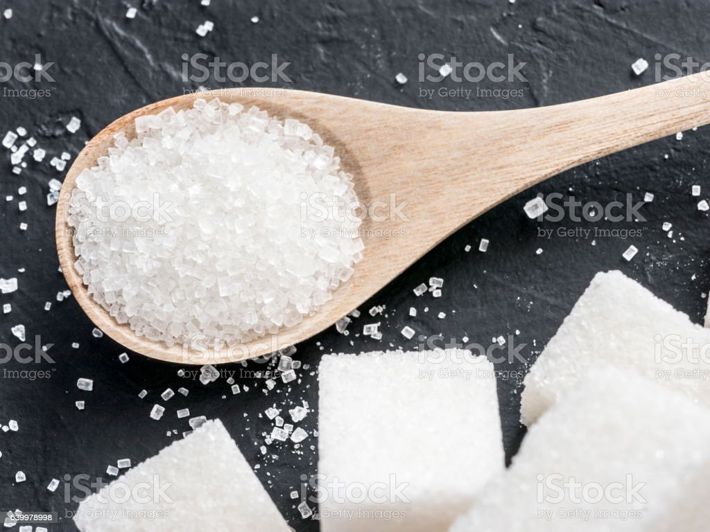 background of white sugar on black stock photo