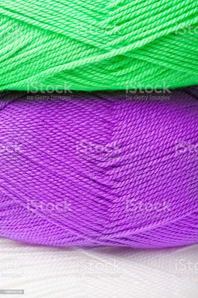 background of yarn skeins in green, purple and white colors stock photo
