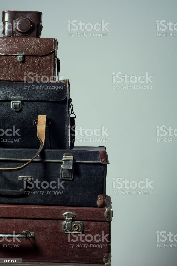Background stack of old shabby suitcases and camera stock photo