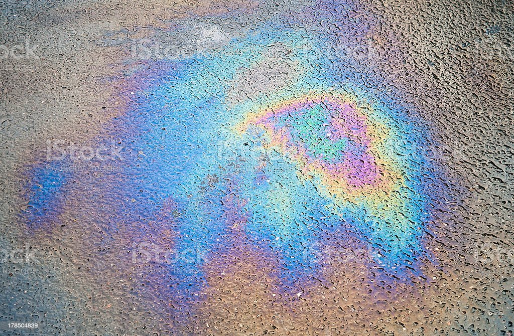 Background texture of an oil spill on asphalt road royalty-free stock photo