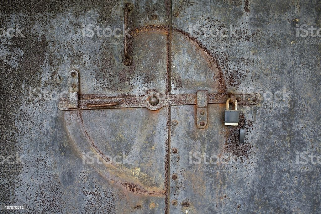Background wallpaper of an old rusted metal door with lock royalty-free stock photo