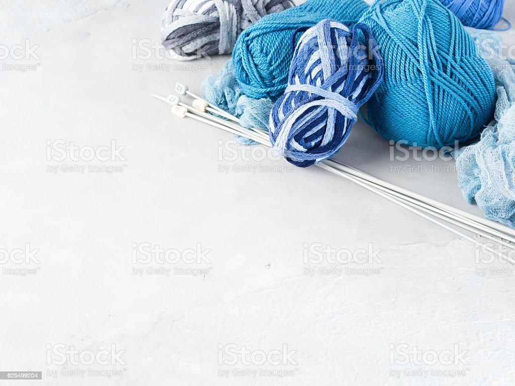 Background with blue yarn and knitting needles stock photo