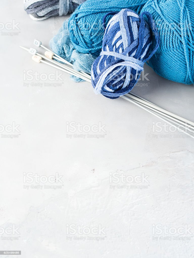 Background with blue yarn and knitting needles. Vertical stock photo