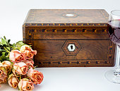 Background with pink dried roses, antique walnut jewelry box wit