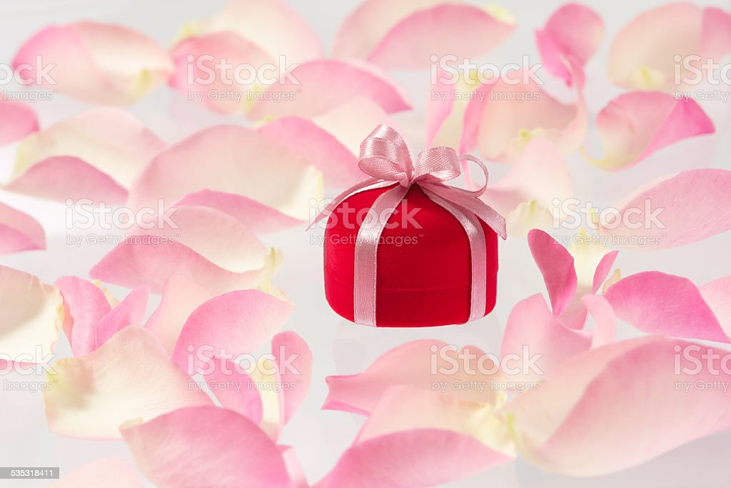 Background with small red velvet ring box and rose petals stock photo