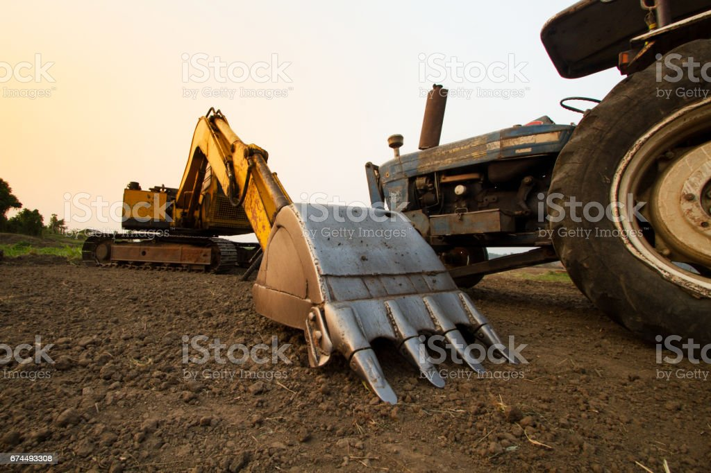 Backhoe and Tractor at cultivated field stock photo