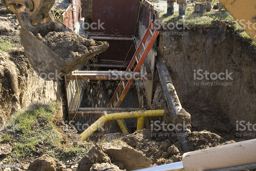 Backhoe Digging around gas and electric utility stock photo