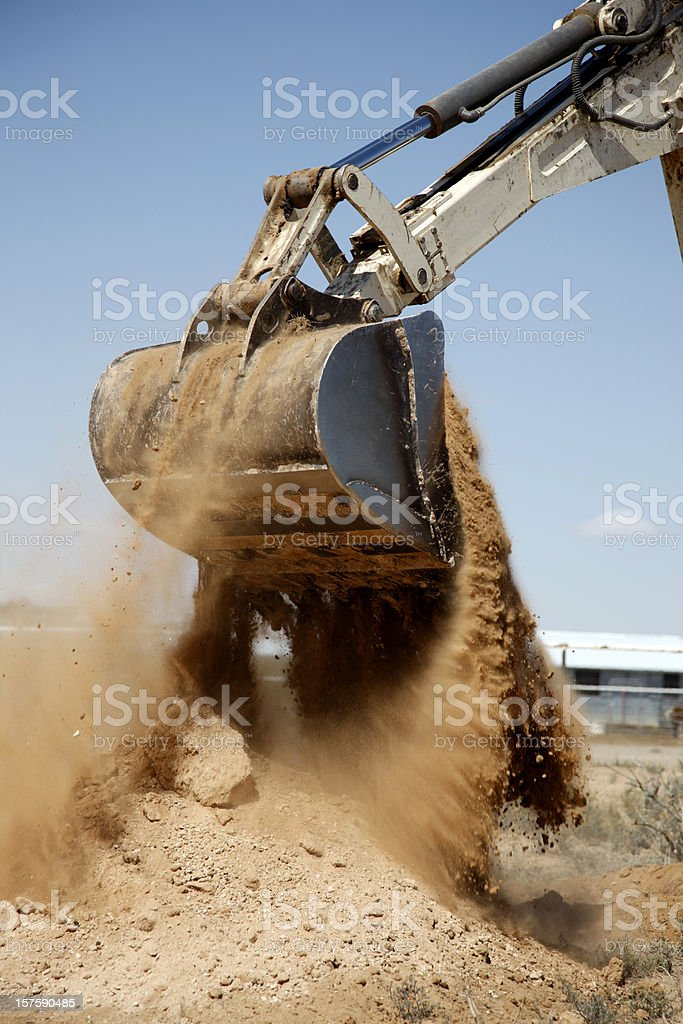 Backhoe Dumping a Scoop of Dirt royalty-free stock photo