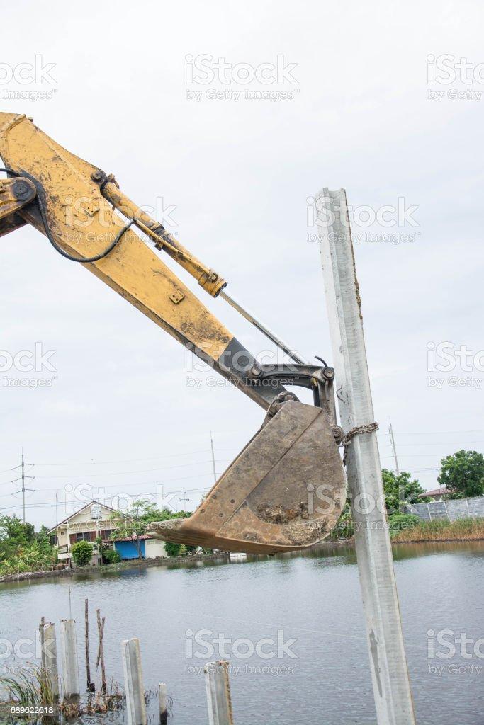 backhoe hoisting concrete pole piles stock photo