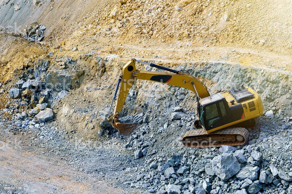 Backhoe loader stone in mine, Big yellow trucks stock photo
