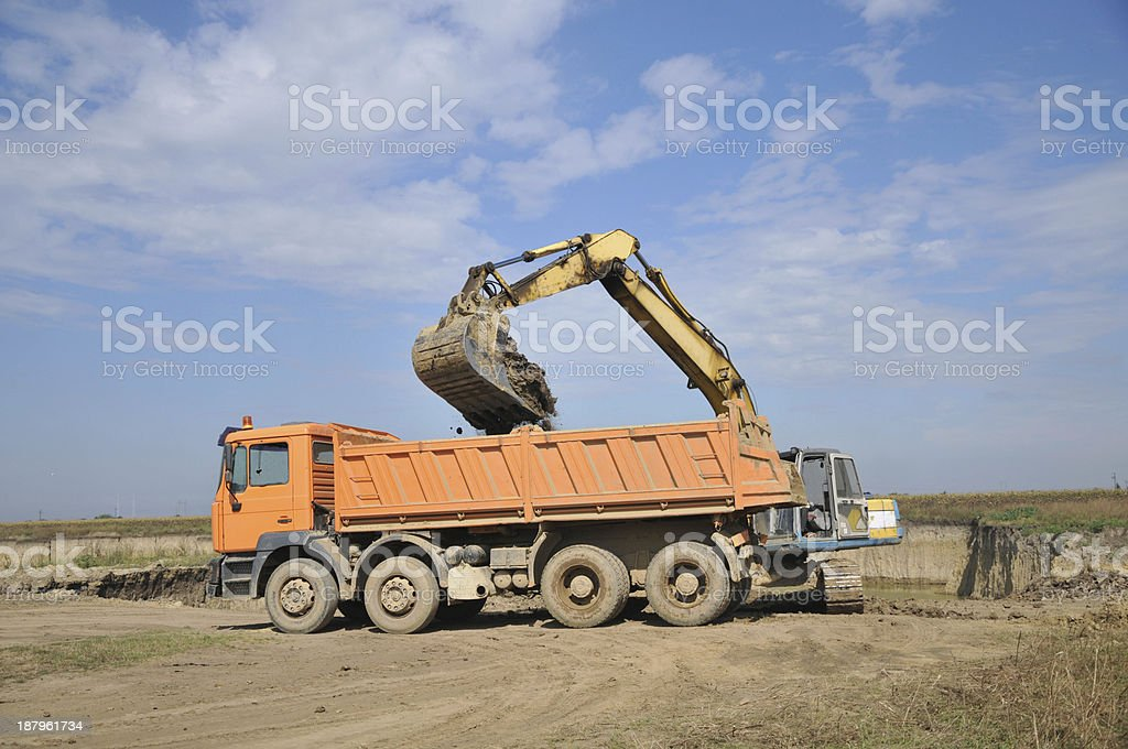 Backhoe loading a dump truck stock photo