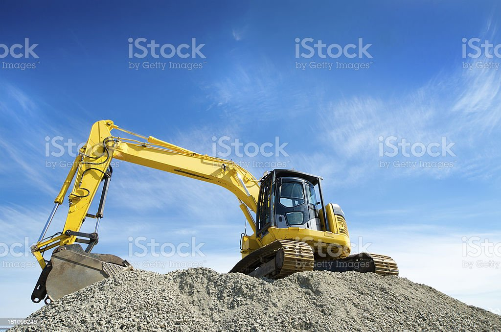 Backhoe on a Gravel Pile stock photo