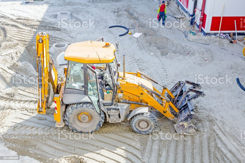 Backhoe tractor is leveling at construction site stock photo