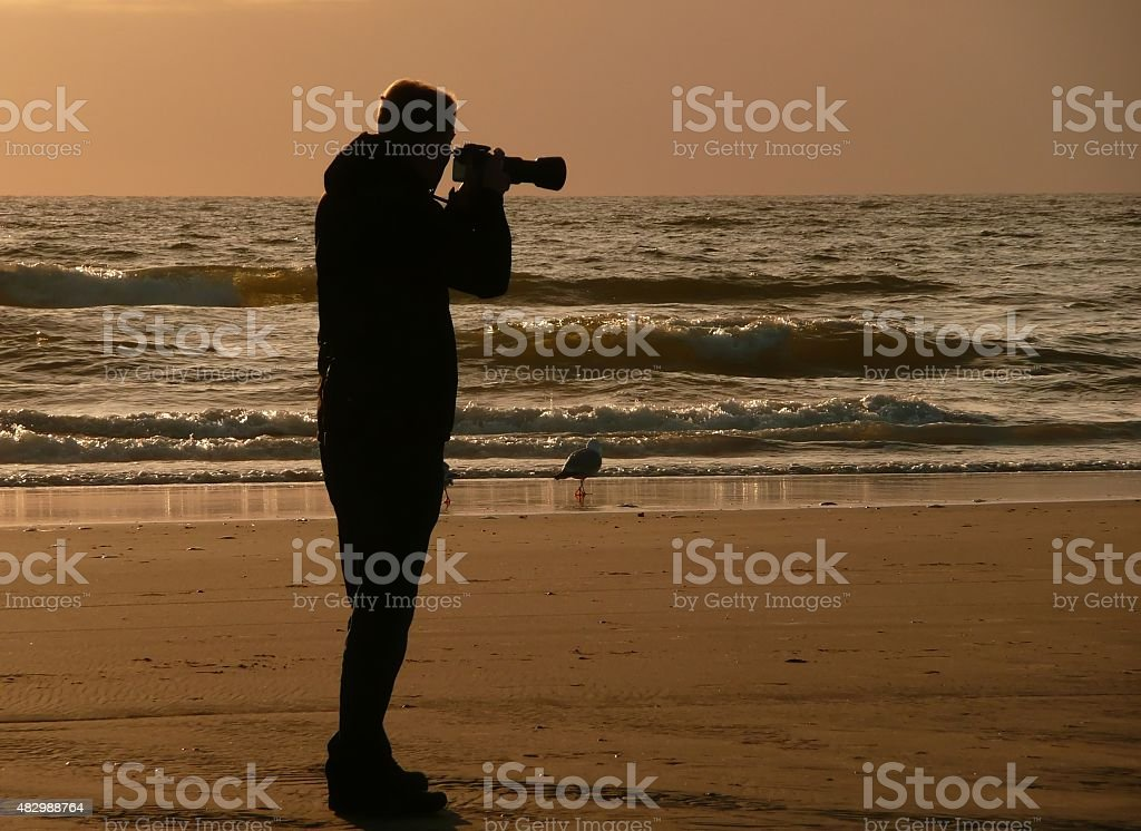 Backlight silhouette of photographer standing upon the foreshore. stock photo