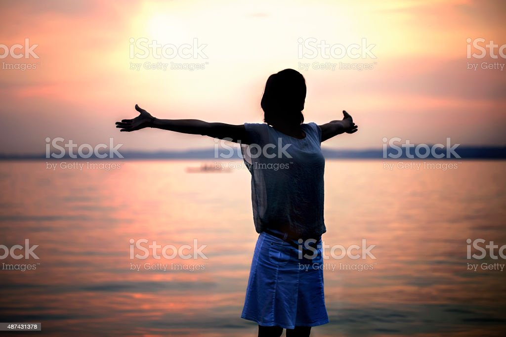 backlight woman taking a deep breath at the sunset stock photo