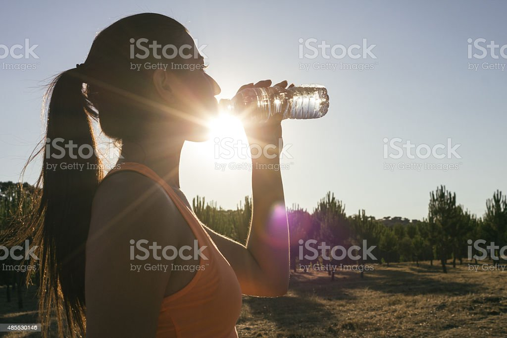 Backlighting of a runner woman drinking water stock photo