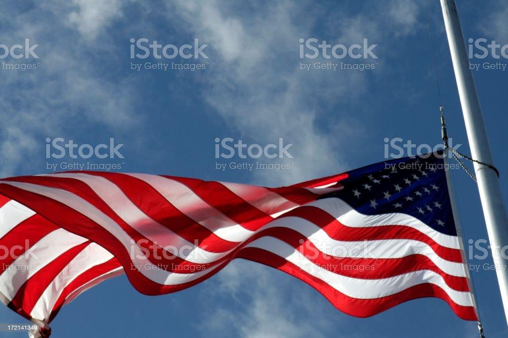 Backlit American Flag at Half-Mast stock photo