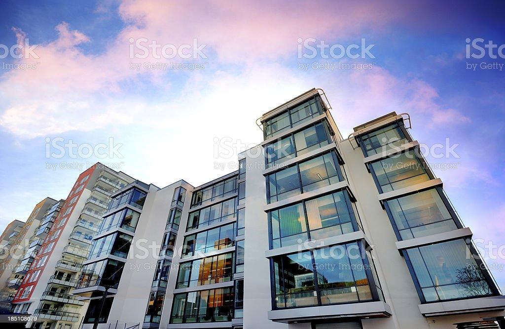 Backlit apartment building against dramatic sky stock photo
