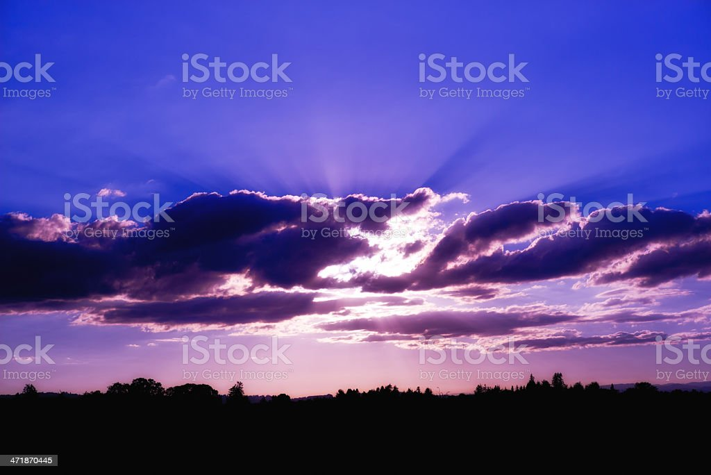 Backlit clouds during a purple sunset royalty-free stock photo