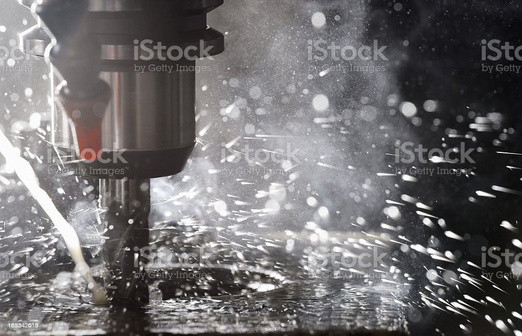Back-lit CNC milling machine in operation cutting steel stock photo