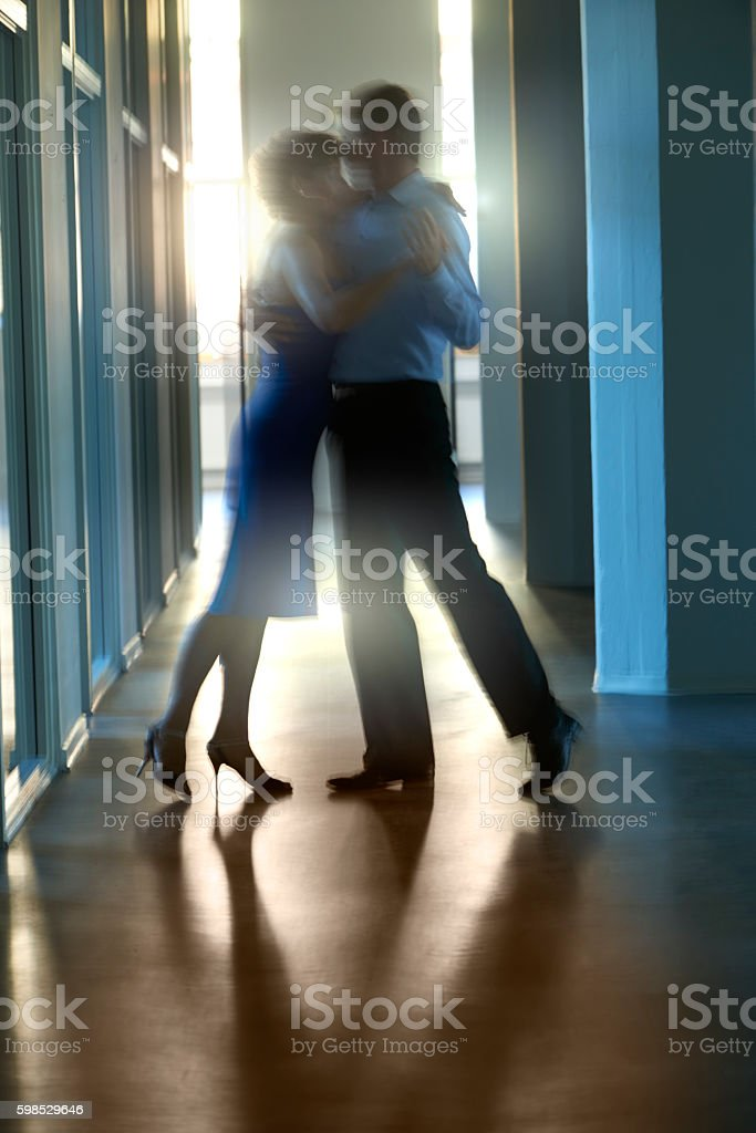 Backlit couple dancing close together stock photo