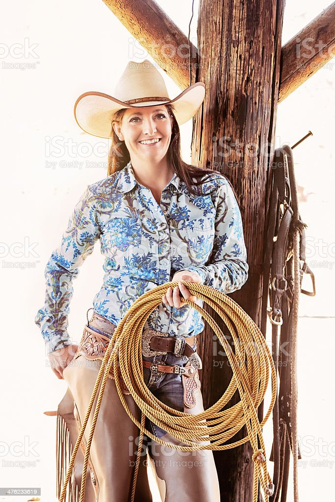 Backlit cowgirl with lasso against corral post royalty-free stock photo