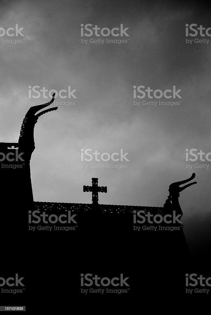 Backlit dragons heads and cross from old stave church royalty-free stock photo