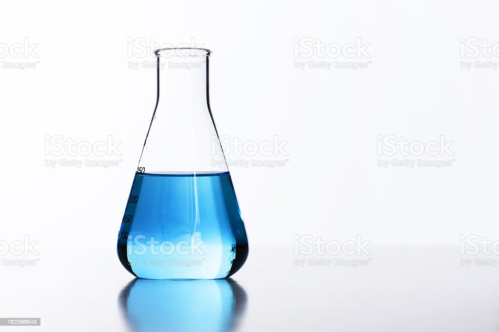 Backlit glass lab flask half filled with blue liquid royalty-free stock photo