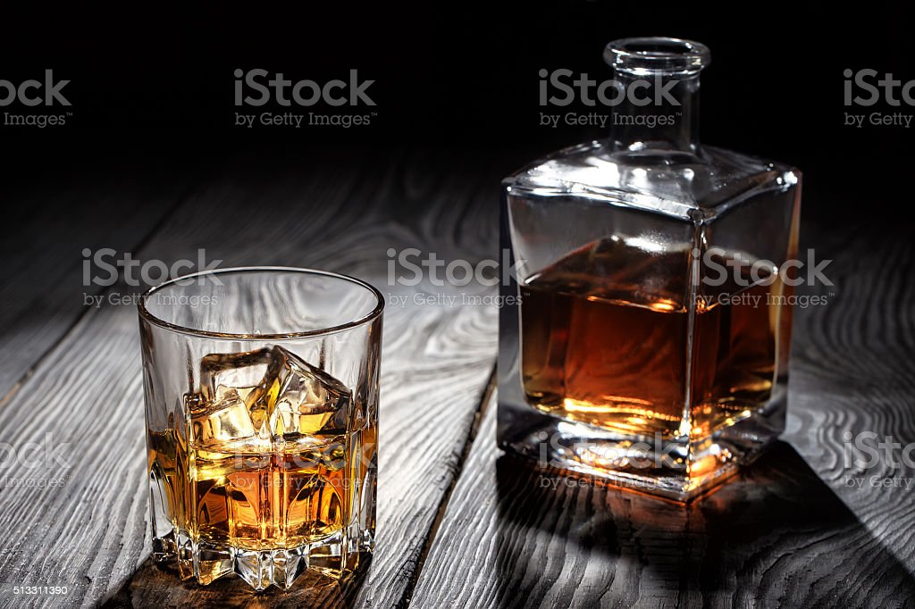 Backlit glass of whiskey with ice stock photo