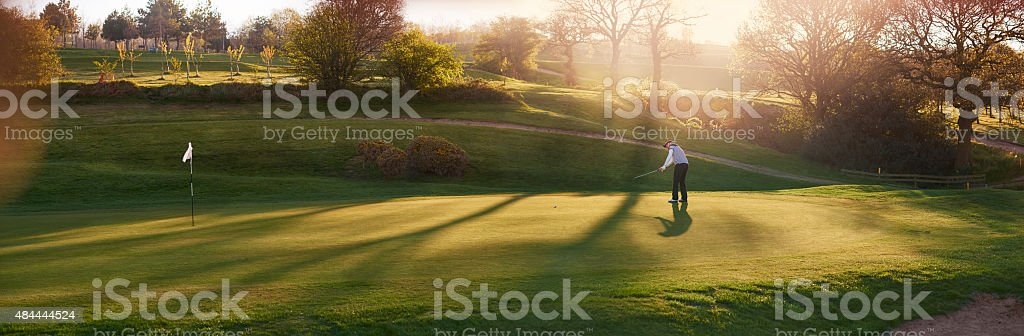 backlit golf course with golfer putting on a green stock photo