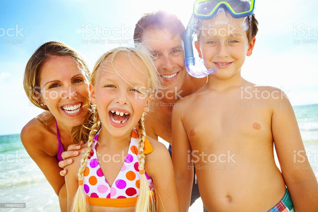 Backlit happy family in bathing suits on the beach royalty-free stock photo