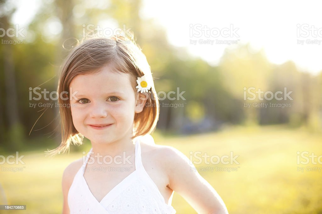 Backlit Image of a girl with flower in her hair royalty-free stock photo