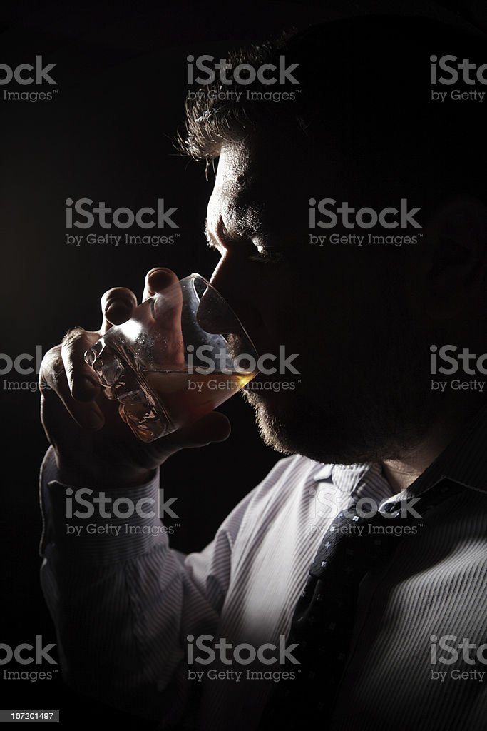 Backlit man drinking alcohol from barware royalty-free stock photo