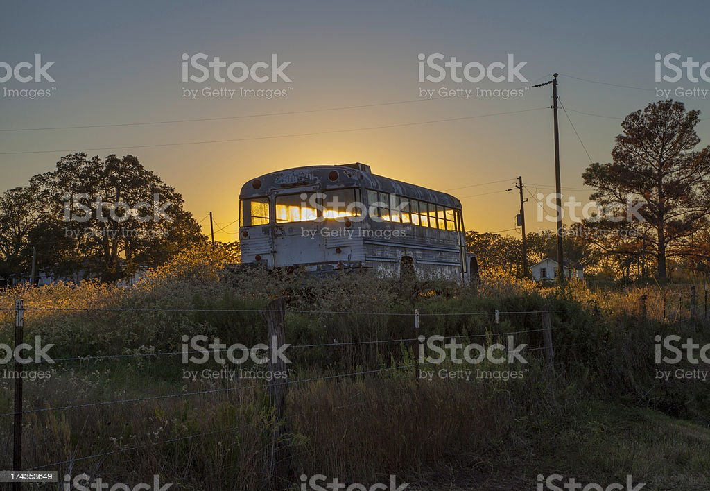 Backlit old school bus in field royalty-free stock photo