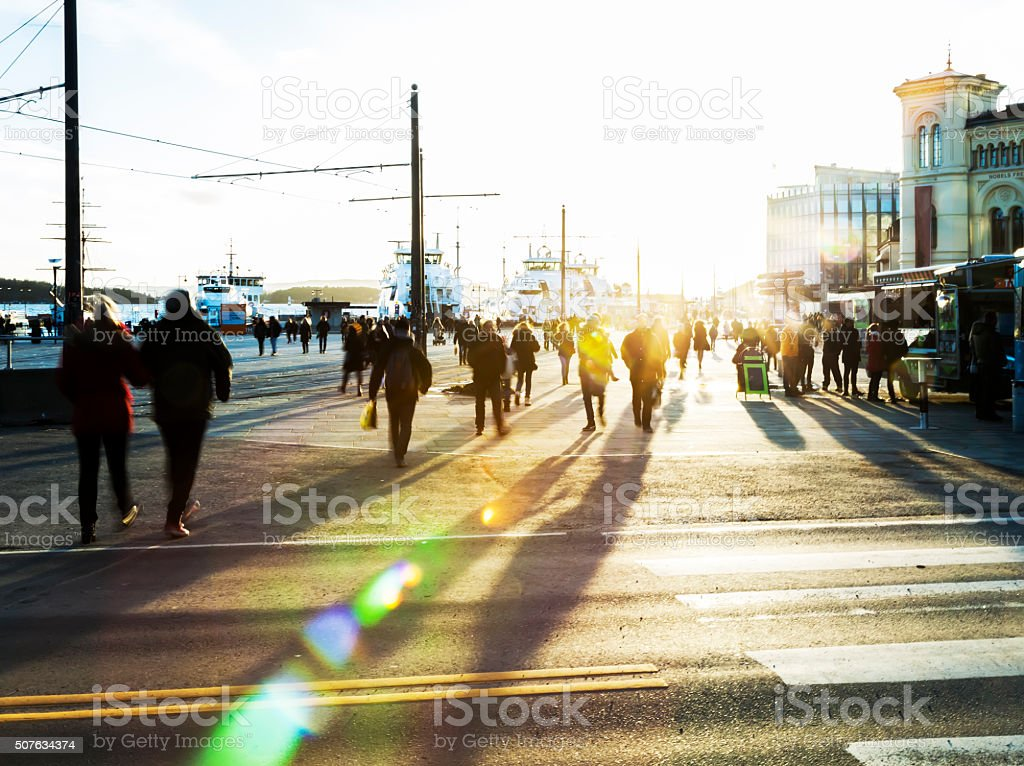 Backlit people  walking in the street at sunset. stock photo