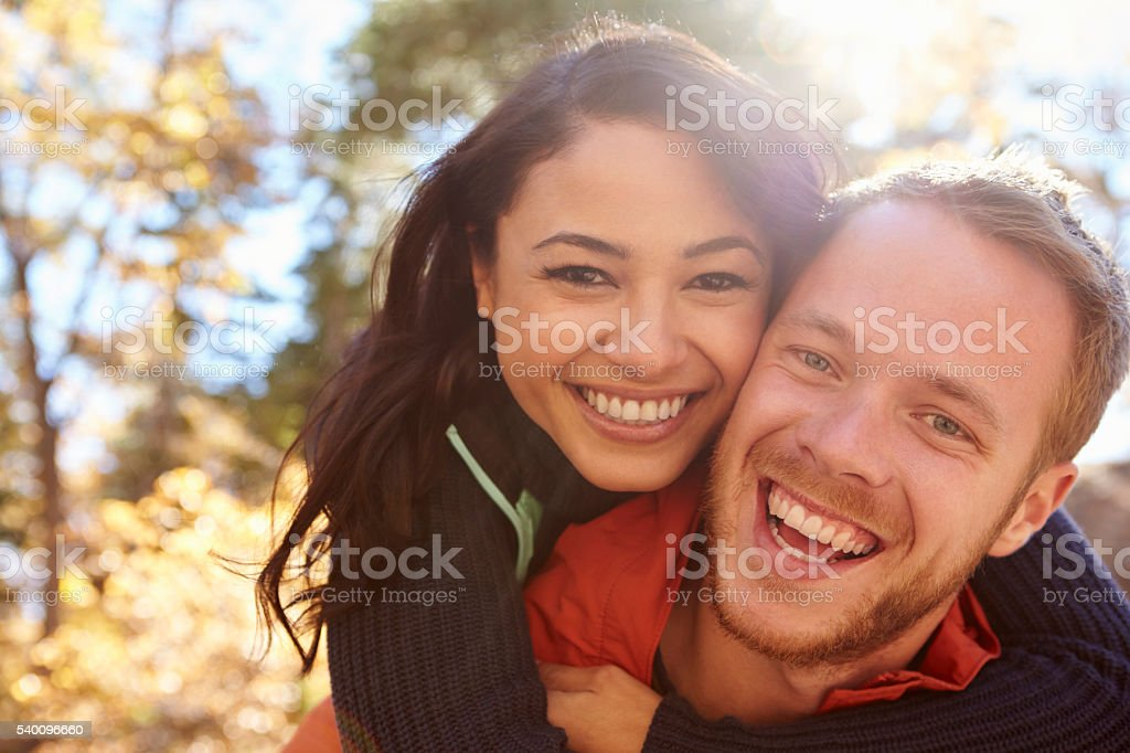 Backlit portrait of mixed race couple embracing in a forest stock photo