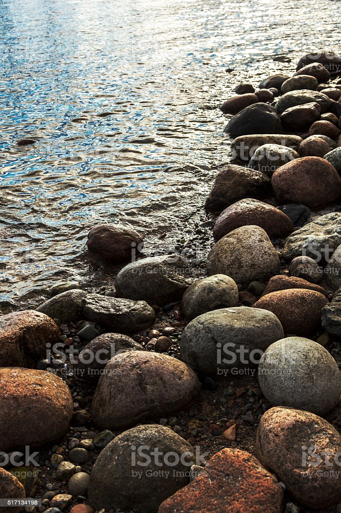 Backlit rounded stones in water on a sandy beach. stock photo