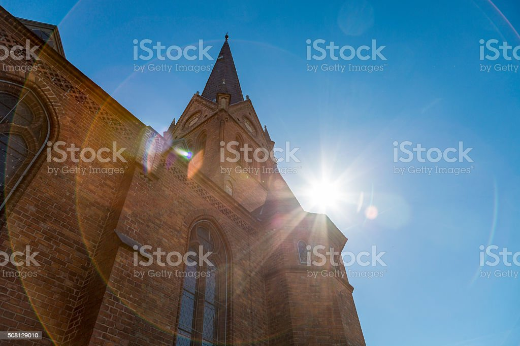 backlit shot of a steeple with the sun behind stock photo