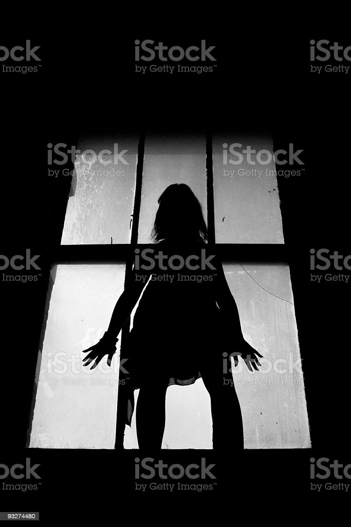 Backlit silhouette of woman in front of window royalty-free stock photo