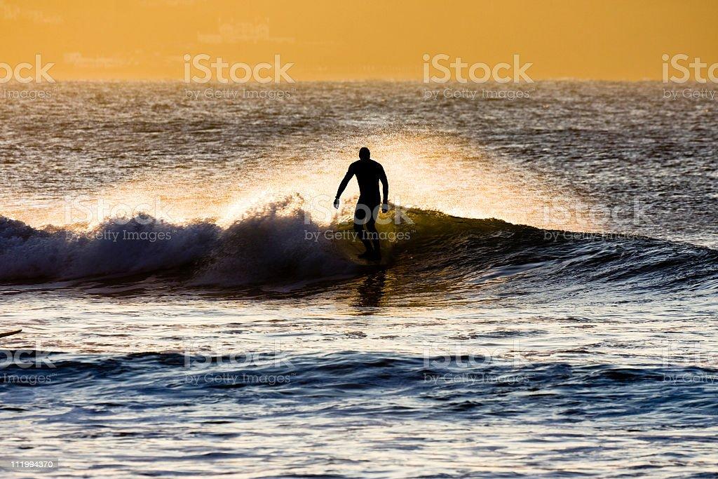 Backlit surfer riding a small wave in Cornwall stock photo